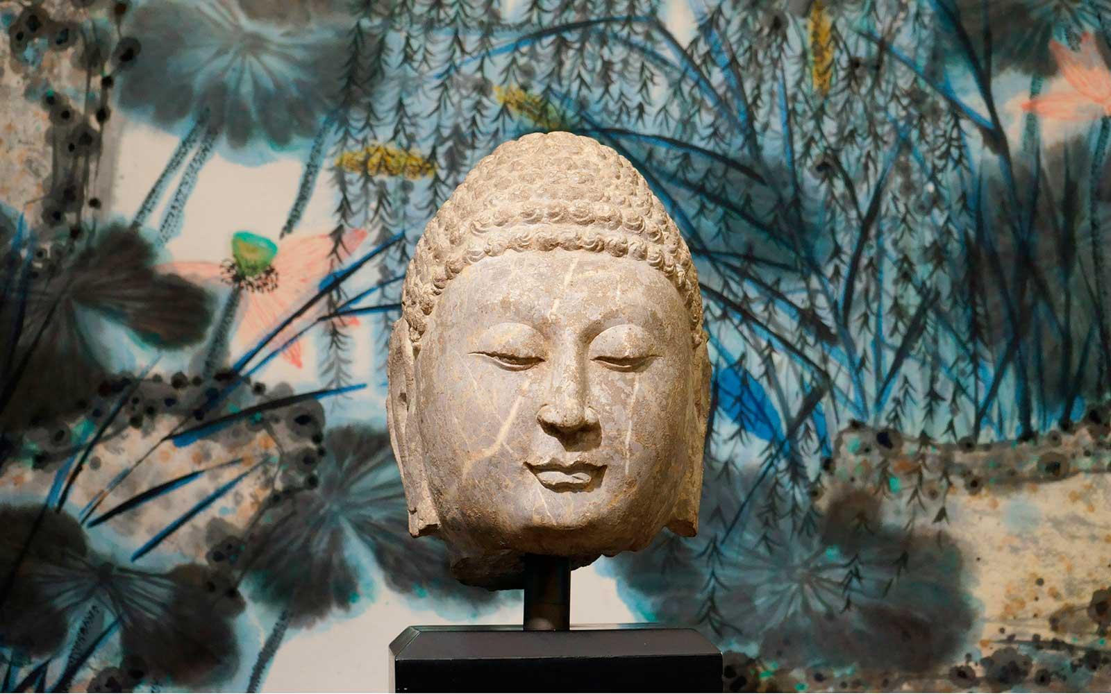 北齊 山東青州佛首 (背景:譚崇憲  「荷塘」紙本設色) Head of Buddha in Limestone, Northern Qi Dynasty (549-577 CE), h38cm.  (Background: <i>Lotus Pond</i> by Tan Chung Hsiang, 2008, ink and color on paper, 360x90cm)
